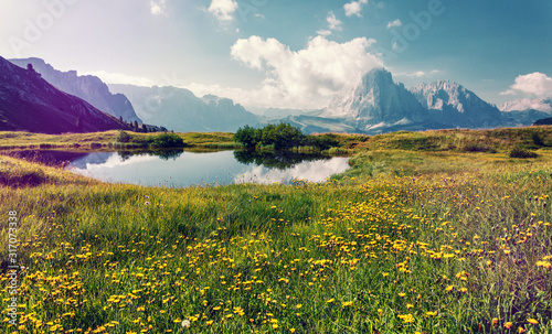 Wall mural - Wonderful Nature Landscape. Spring landscape at sunny day. perfect countryside scenery with blue sky and blooming hillside, clear lake. Val Gardena. Dolomites Alps. Italy. Travel Lifestyle concept.