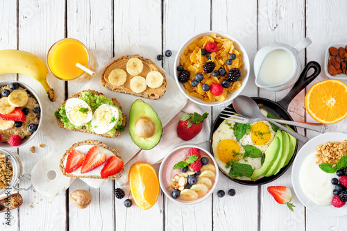 Obraz Healthy breakfast table scene with fruits, yogurts, oatmeal, cereal, smoothie bowl, nutritious toasts and egg skillet. Top view over a white wood background. - fototapety do salonu