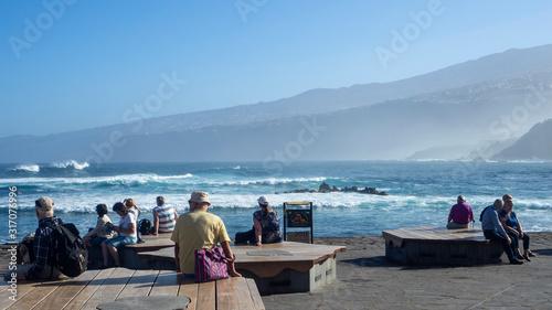 grupo de jubilados disfrutando del paisaje del mar con montañas al fondo Canvas Print