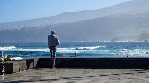 Photo un hombre mayor mirando el mar con la montaña al fondo