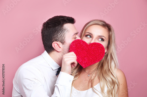 Obraz Young couple holding red love heart over eyes and kissing - fototapety do salonu