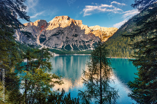 Fotomurales - Incredible view on majestic famouse lake Braies during sunrise. Wonderful sunny landscape in dolomites Alps with perfect sky. Amazing nature Scenery. Lake Braies is also known as Lago di Braies