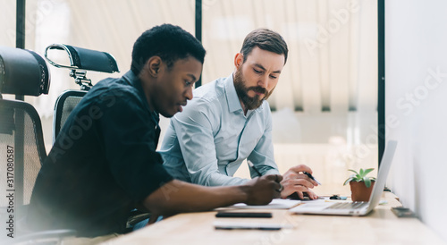 Foto Pensive adult multiethnic coworkers working on project in light modern office
