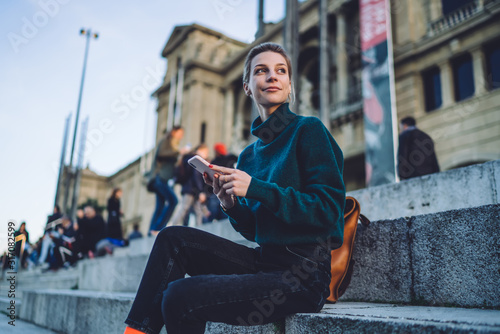 Attractive Caucasian tourist with smartphone device looking away and pondering on journey trip during free time for rest in historic center, beautiful millennial generation using cellular outdoors #317082599