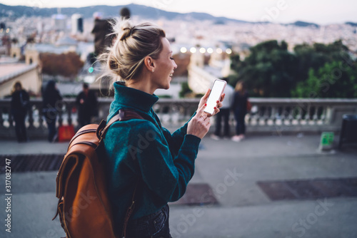 Foto Joyful female tourist with smartphone exploring city