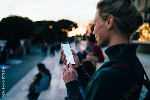 Fotomural Glad female tourist looking on smartphone during walk around city