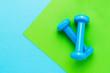 Leinwandbild Motiv Blue dumbbells lie on green-blue background. The concept of healthy lifestyle. Copy space, top view