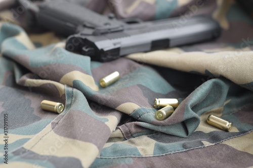 9mm bullets and pistol lie on folded camouflage green fabric Wallpaper Mural