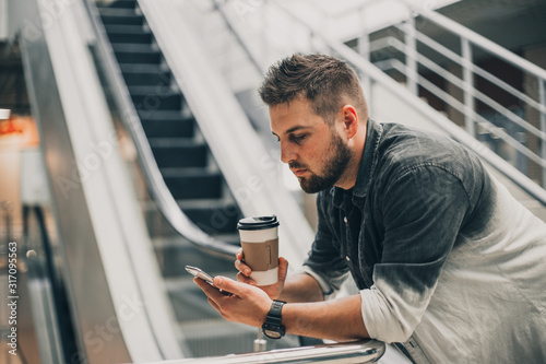 Cuadros en Lienzo Young handsome man in shirt walking in city mall with cup of coffee and smartphone