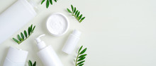 Natural Organic SPA Cosmetic Products Set With Green Leaves. Top View Herbal Skincare Beauty Products On Green Background. Banner Mockup For Eco Shop Or Beauty Salon. Flat Lay Minimalist Style