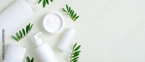 fototapeta na drzwi i meble Natural organic SPA cosmetic products set with green leaves. Top view herbal skincare beauty products on green background. Banner mockup for eco shop or beauty salon. Flat lay minimalist style