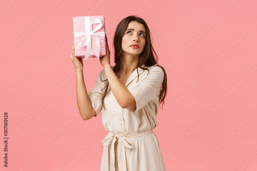 Fototapeta Celebration, women and anticipation concept. Alluring curious young woman shaking gift box with interest, focus, intrigued what inside, standing pink background, receive present