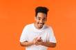 canvas print picture - Lifestyle, modern people, emotions concept. Happy handsome young african-american man with moustache and afro haircut, laughing clap hands, relish good deal, feeling good, orange background