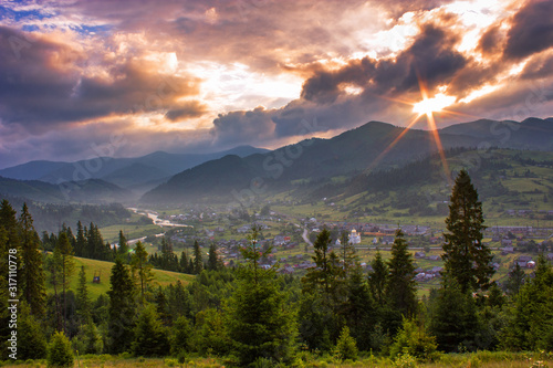 Obraz summer mountains view, magnificent morning landscape in Carpathians, scenic sunrise in valley with river and village and hills covered forest, first rays of sun, Ukraine, Carpathians, Europe - fototapety do salonu