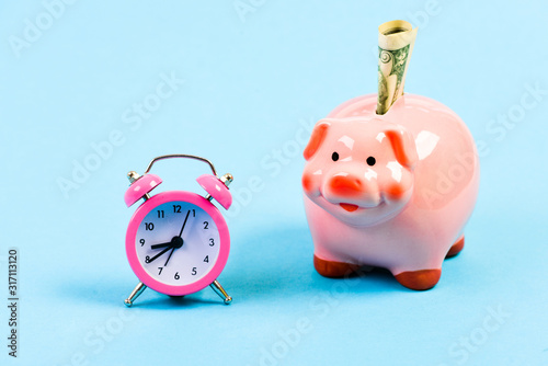 Fototapeta Banking account. Bankruptcy and debt. Pay for debt. Bank collector service. Credit debt. Economics and finance. It is time to pay. Piggy bank stuffed dollar cash and alarm clock. Financial crisis obraz