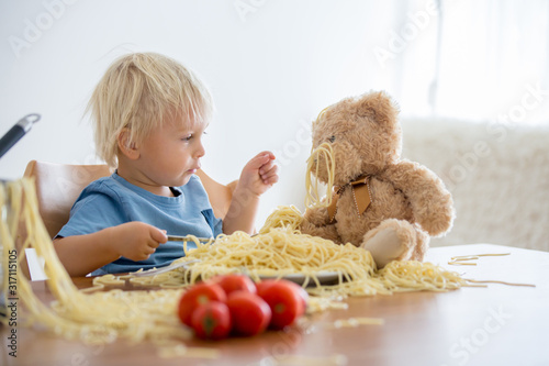 Little baby boy, toddler child, eating spaghetti for lunch and making feeding teddy bear friend