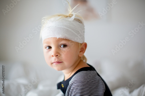 Obraz na plátně Close portrait of little toddler boy with head injury, sitting in bed, tired