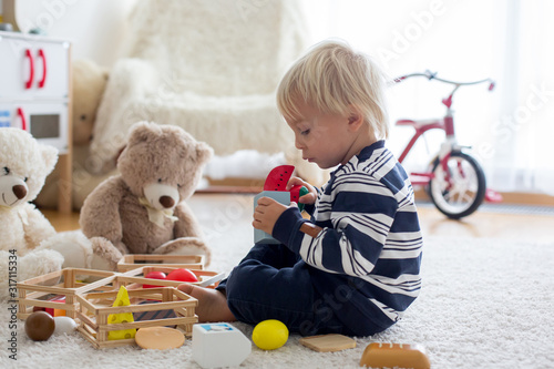 Photo  Sweet toddler boy, playing with teddy bears and wooden toys from kids kitchen se
