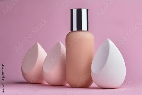 Conatainer with fluid foundation with beauty blender.Cosmetic branding, glamour and skincare concept - Tonal bb cream bottle make-up fluid foundation base for nude skin color on pink background - 317125349