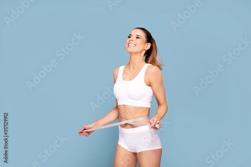 Active happy fit girl with centimeter. Fototapeta