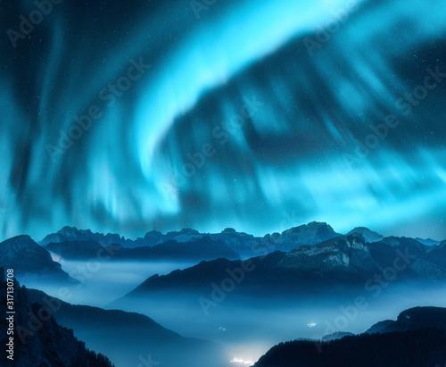 Fotografie, Tablou Aurora borealis above the mountains in fog at night