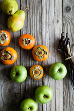 Persimmon And Apples On A Wood...