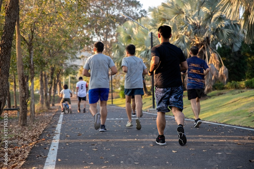 group of runners running down road in autumn sunset Park with fallen yellow leaves. healthy, lifestyle concept