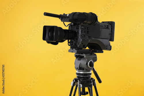 Obraz Modern professional video camera on yellow background - fototapety do salonu