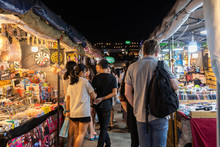 Tourist And Locals Walking And Shopping At Rachada Night Train Market (Talad Rot Fai). Market With Plenty Of Shops With Colorful Canvas Roofs At Night In Bangkok, Thailand
