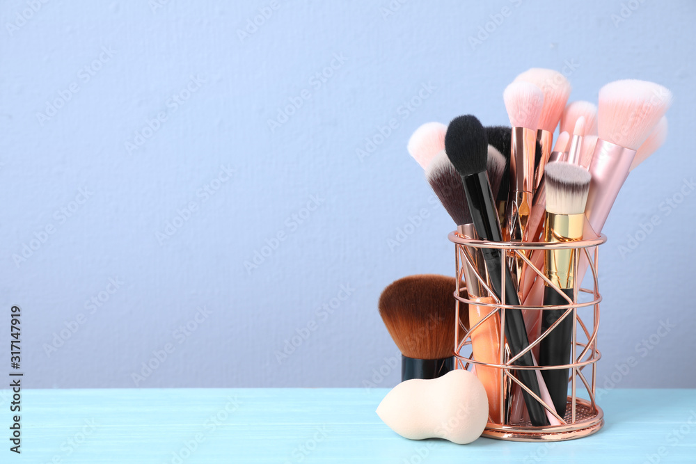 Fototapeta Set of professional makeup brushes in holder on blue wooden table. Space for text