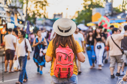 Fototapeta Back side of Young Asian traveling women walking and looking in chatujak weekend walking street market in evening time at Bangkok, Thailand, traveler and tourist,walking street and food market concept obraz