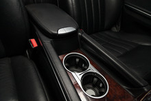Interior View With Leather Seats And Two Cupholders And Armrest Of Black Used Car Stands In The Showroom After Dry Washing Before Sale