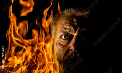 The portrait of an older man is surrounded by flames Wallpaper Mural