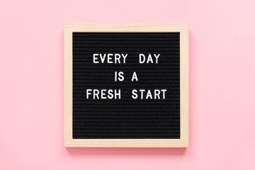Every day is a fresh start. Motivational quote on black letter board on pink background. Concept inspirational quote of the day. Greeting card, postcard.