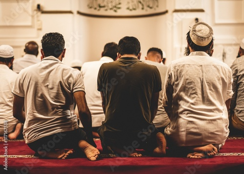 Fotografie, Tablou Closeup shot of Muslim people worshiping in the mosque