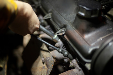 Crash on the road. Car repair. Engine on the hood. A man is looking for a breakdown in his car. Details of the construction of personal vehicles. Diagnosis of damage inside the mechanism.