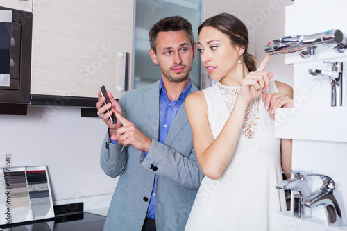 Fototapeta Couple choosing new mixer tap