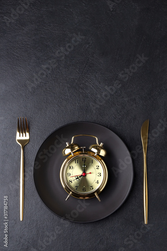 Fototapeta Interval fasting concept with a golden alarm clock on a black plate obraz