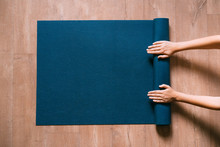Fit Woman Folding Blue Exercise Mat On Wooden Floor Before Or After Working Out In Yoga Studio Or At Home. Equipment For Fitness, Pilates Or Yoga, Well Being Concept. Flat Lay, Space For Text.