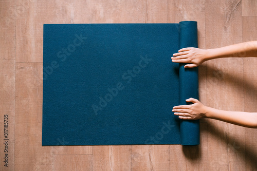 Obraz Fit woman folding blue exercise mat on wooden floor before or after working out in yoga studio or at home. Equipment for fitness, pilates or yoga, well being concept. Flat lay, space for text. - fototapety do salonu