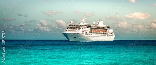 Fototapeta Cruise ship sailing on the Caribbean Sea. Side view of the vessel. Wide image. obraz