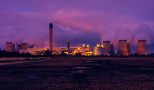 Drax, North Yorkshire, UK  On A Cold Winter's Night. The Bright Lights Of A Power Station Are Reflected In  A Waterlogged Farmer's Field. Plumes Of Water Vapour From The Cooling Towers Fill The Sky