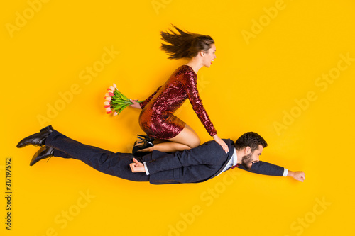 Fototapeta Top above high angle full body profile side photo ideal dream date concept two people man fly girl sit back spine hold tullips wear red short dress tux suit lay isolated yellow color background obraz