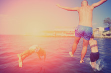 Group Of Happy People Having Fun Jumping In The Sea Water From A Pier. Summer Vacation On Sea Coast. Three Young Men Dive In Water On Ocean Pool Party. Concept Of A Healthy Lifestyle, Youth Friendship