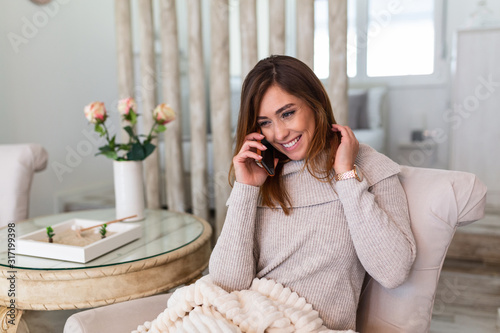 Fototapeta Happy young woman caller talking on her mobile phone at home, cheerful teen girl