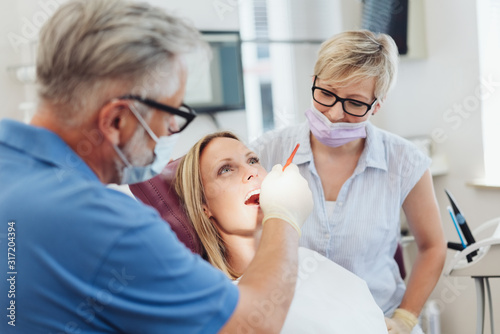 Fotomural Dentist examining the teeth of a female patient