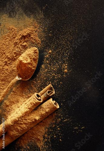 Valokuva Cinnamon sticks and cinnamon powder on a dark background