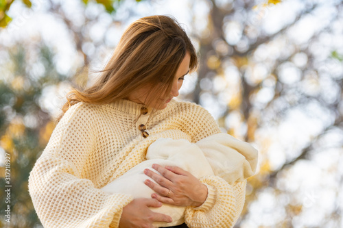 Valokuva Young girl feeds newborn baby in park