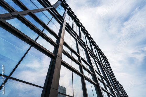 Fototapeta Clouds reflected in windows of modern office building obraz