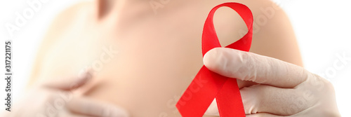 Female hand in gloves holding red ribbon cancer symbol breast closeup on doctor mammology clinic reception Canvas Print